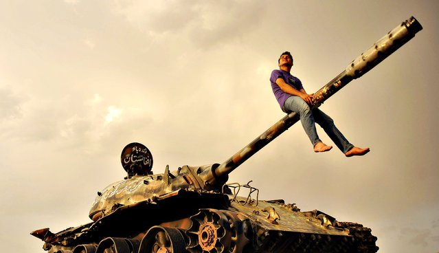 An Afghan youth sits astride the gun barrel of a Soviet-era tank, in Kabul, Afghanistan, 29 August 2014. Soviet troops occupied the country for ten years from 1979 to 1989. (Photo by Jawad Jalali/EPA)