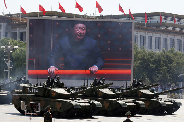 Chinese President Xi Jinping is displayed on a screen as Type 99A2 Chinese battle tanks take part in a parade commemorating the 70th anniversary of Japan's surrender during World War II held in front of Tiananmen Gate in Beijing, Thursday, September 3, 2015. (Photo by Ng Han Guan/AP Photo)