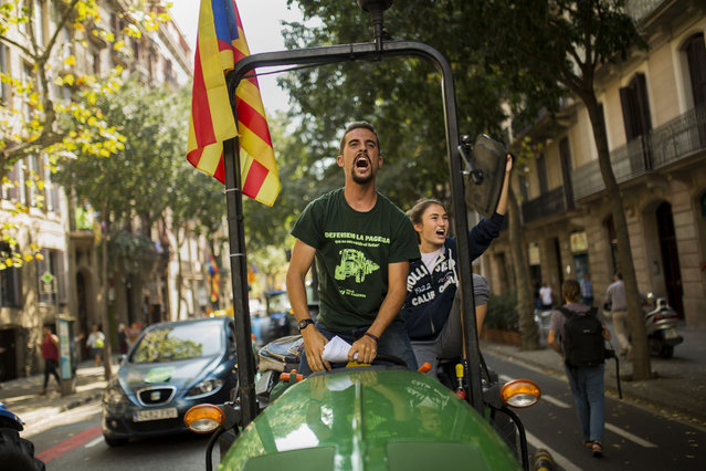 """A man with the estelada, or independence flag, shouts slogans as he steers a tractor during a protest by farmers in Barcelona, Friday, September 29, 2017. Authorities in Catalonia aim to ensure that a disputed referendum on independence from Spain will take place peacefully on Sunday despite a crackdown on the vote by the national government, the region's interior chief said. The small placard read: """"Freedom"""". (Photo by Francisco Seco/AP Photo)"""