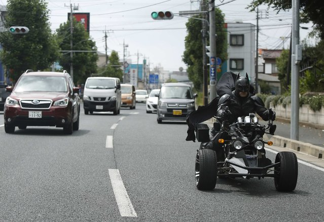"""A 41-year-old man going by the name of Chibatman rides his """"Chibatpod"""" on the road in Chiba, east of Tokyo, August 31, 2014. The man, who dresses up as the comic book superhero Batman, came up with his moniker after adding a prefix of the first three letters of the city name, of which he roams on his three-wheeled motorcycle. (Photo by Yuya Shino/Reuters)"""
