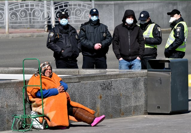 An elderly homeless woman asks for alms as police wearing face masks, amid concerns over the spread of the novel coronavirus COVID-19, patrol the streets of the Ukrainian capital of Kiev on April 5, 2020 a day before the lockdown tightening, imposed by authorities to attempt to prevent the spread of COVID-19 coronavirus disease. (Photo by Sergei Supinsky/AFP Photo)