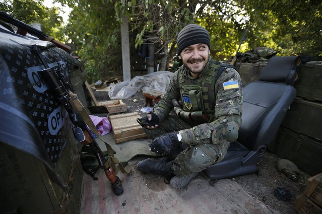 A Ukrainian serviceman sits at his entrenchment near Donetsk, September 16, 2014. Russia threatened to send more troops to its newly-annexed territory of Crimea on Tuesday, after NATO began exercises in western Ukraine while Kiev's forces are fighting pro-Russian separatists in the east. (Photo by David Mdzinarishvili/Reuters)