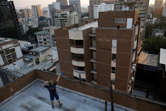 Francisco throws a plastic container filled with wine to another rooftop during a nationwide quarantine due to the coronavirus disease (COVID-19) outbreak in Caracas, Venezuela on April 6, 2020. (Photo by Manaure Quintero/Reuters)