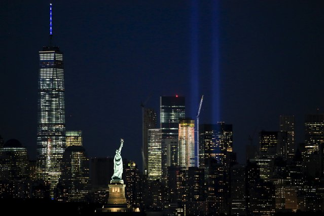 The Tribute in Light is illuminated next to the Statue of Liberty (C) and One World Trade Center (L) during events marking the 14th anniversary of the 9/11 attacks on the World Trade Center in New York September 11, 2015. (Photo by Eduardo Munoz/Reuters)