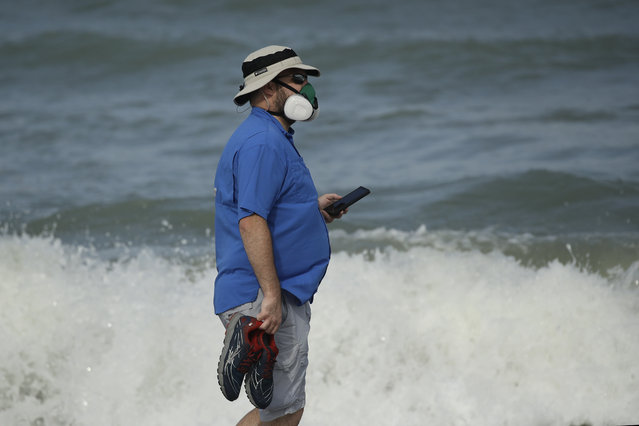 A man wears a mask to help prevent the spread of the coronavirus as he walks alone on the beach Sunday, May 31, 2020, at Satellite Beach, Fla. (Photo by Charlie Riedel/AP Photo)