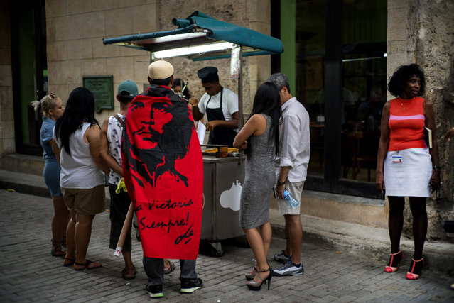 """The Mexican tourist Carlos Lome Morales wears a Che Guevara flag over his shoulders, as he lines up at a street stall to buy churros, in Havana, Cuba,Monday, May 23, 2016. The flag has a quote by Guevara that reads in Spanish """"To victory always"""". (Photo by Ramon Espinosa/AP Photo)"""