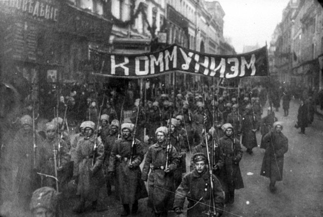 In this photo taken in October 1917, provided by Russian State Documentary Film and Photo Archive, Russian State Documentary Film and Photo Archive, armed soldiers carry a banner reading 'Communism' march alone Nikolskaya street towards to the Kremlin Wall in Moscow, Russia. The 1917 Bolshevik Revolution was long before the digital revolution allowed anyone to instantly document events. But the clumsy cameras of the time still caught some images that capture the period's drama. (Photo by Russian State Documentary Film and Photo Archive via AP Photo)