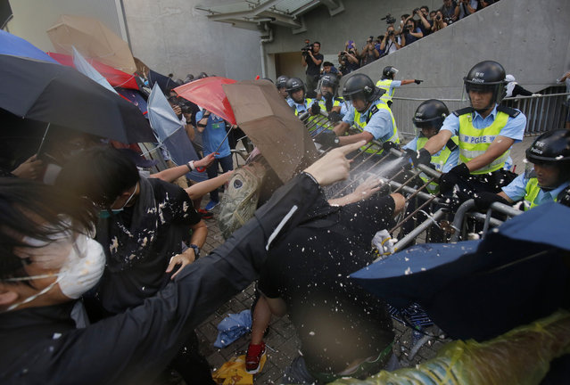 Riot police fire pepper spray into the crowds as thousands of protesters surround the government headquarters in Hong Kong Sunday, September 28, 2014. Hong Kong police used tear gas on Sunday and warned of further measures as they tried to clear thousands of pro-democracy protesters gathered outside government headquarters in a challenge to Beijing over its decision to restrict democratic reforms for the city. (Photo by Wally Santana/AP Photo)