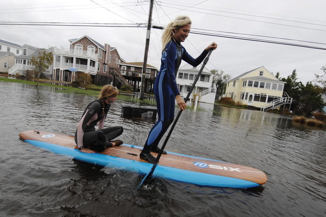Jenna Webb (L), 18, and Zoe Jurusik, 20, paddle-board down a flooded city street in the aftermath of Hurricane Sandy in Bethany Beach, Delaware, October 30, 2012. Millions of people were left reeling in the aftermath of monster storm Sandy on Tuesday as New York City and a wide swathe of the eastern United States struggled with epic flooding and massive power outages. (Photo by Jonathan Ernst/Reuters)