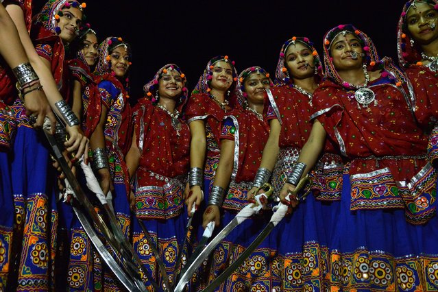 """Young Indian girls from the Shatriya or Rajput communities pose prior to the start of the """"Talwar No Garbo"""" or """"Traditional Dance with Swords"""" organised by the Vasna Paldi Rajput Samaj on the third day of the """"Nine Nights of Navratri"""" festival in Ahmedabad on late September 27, 2014. The annual, nine-night Navratri Hindu festival, which began on September 25, is celebrated in many parts of the country with music, prayer and dance. (Photo by Sam Panthaky/AFP Photo)"""