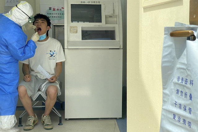 A resident gets tested at a fever clinic in Beijing Monday, June 15, 2020. China's capital was bracing Monday for a resurgence of the coronavirus after more than 100 new cases were reported in recent days in a city that hadn't seen a case of local transmission in more than a month. (Photo by Ng Han Guan/AP Photo)