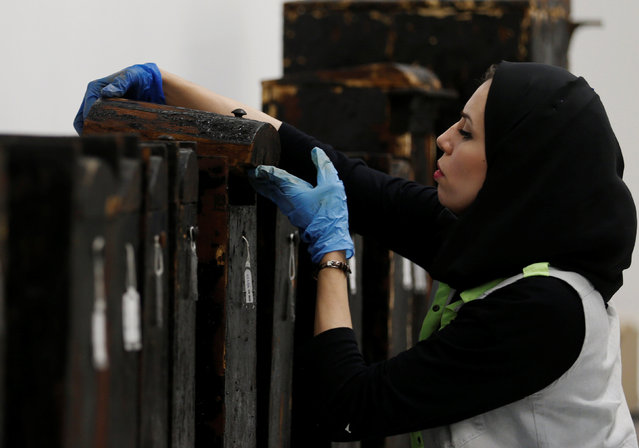 An Egyptian archeological technician works with the remains of pharaoh King Tutankhamun in the Wood Laboratory of the conservation centre of the Grand Egyptian Museum, under construction, on the outskirts of Cairo, Egypt August 21, 2016. (Photo by Amr Abdallah Dalsh/Reuters)