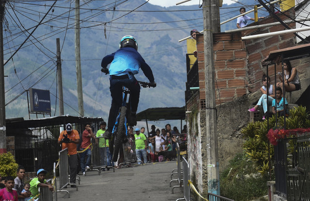 People look at a downhill rider during the Urban Bike Inder Medellin race final at the Comuna 1 shantytown in Medellin, Antioquia department, Colombia on November 19, 2017. (Photo by Joaquin Sarmiento/AFP Photo)