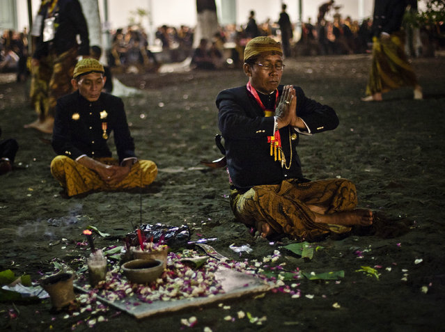 "Javanese people pray before rituals night carnival ""1st Suro"" (Javanese calender) during  Islamic New Year celebrations at Kasunanan Palace on November 14, 2012 in Solo City, Central Java, Indonesia. Javanese will celebrate the national holiday with ceremonies and rituals marking the 1434th Islamic New Year's Eve or ""1st Suro"". The parade started from Keraton Kasunanan and is headed by a group of albino buffaloes, known as Kebo Bule. Local people believe that the parade of Heirlooms and Kebo Bule will bring them a better life. (Photo by Ulet Ifansasti)"