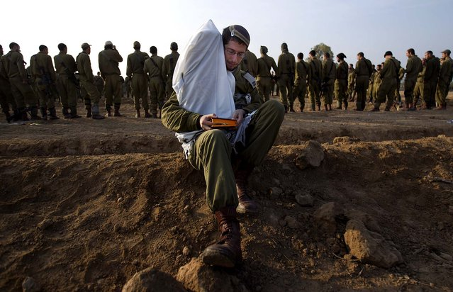 An Israeli officer holds a Torah as he reads from a holy book while others gather in a staging area near the Israel – Gaza Strip border on Monday. (Photo by Ariel Schalit/Associated Press)