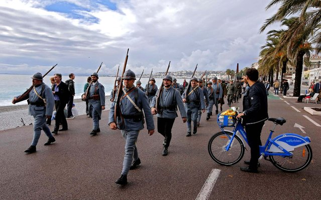 "Citizens of the southern French town of Nice, wearing ""Poilu"" or French World War I infantry uniforms, parade on the city's promenade des Anglais during an Armistice Day ceremony, November 11, 2012. November 11 marks the signing of the truce that ended the fighting in World War I , and is the day the more than 1 million French soldiers killed in that war are memorialized. (Photo by Lionel Cironneau/Associated Press)"