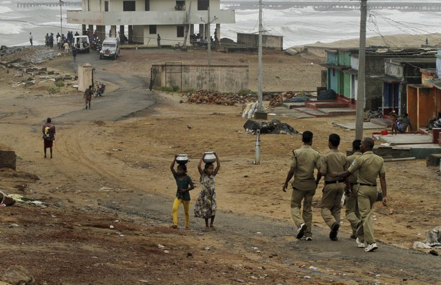 Indian children walk carrying water as policemen arrive to evacuate people on the Bay of Bengal coast at Gopalpur, Orissa, about 285 kilometers (178 miles) north east of Visakhapatnam, India, Sunday, October 12, 2014. (Photo by Biswaranjan Rout/AP Photo)
