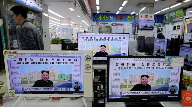 A man walks past TV monitors displaying a news program at an electronic shop in Seoul, South Korea, Tuesday, October 14, 2014, showing a North Korean newspaper with a photo of North Korean leader Kim Jong Un smiling, reportedly during his first public appearance in five weeks in Pyongyang, North Korea. (Photo by Ahn Young-joon/AP Photo)