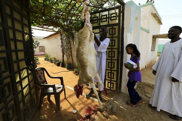 Men hang a slaughtered sheep at the door of a house after performing Eid al-Adha prayers in Khartoum, Sudan September 24, 2015. (Photo by Mohamed Nureldin Abdallah/Reuters)