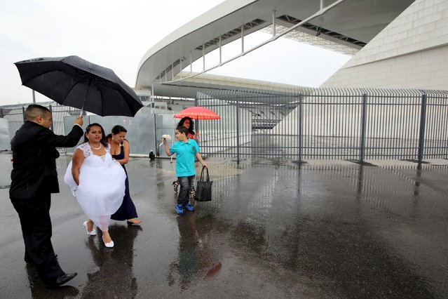 A couple and their relatives arrive at Arena Corinthians soccer stadium to attend a mass wedding ceremony in Sao Paulo, Brazil, September 26, 2015. (Photo by Paulo Whitaker/Reuters)