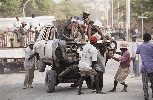 Haitians pull a car atop a pushcart in Port-au-Prince, October 11, 1994. The price of gasoline has fallen to about $6 US per gallon since U.S. forces occupied Haiti. Before, gasoline had cost as much as $10 U.S. per gallon. (Photo by Eric Draper/AP Photo)