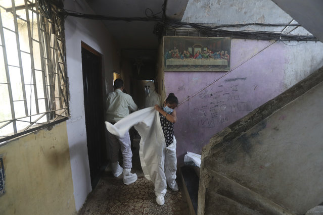 A health worker puts on a protective suit before screening people for COVID-19 symptoms at residential building in Dharavi, one of Asia's biggest slums, in Mumbai, India, Friday, July 17, 2020. India crossed 1 million coronavirus cases on Friday, third only to the United States and Brazil, prompting concerns about its readiness to confront an inevitable surge that could overwhelm hospitals and test the country's feeble health care system. (Photo by Rafiq Maqbool/AP Photo)
