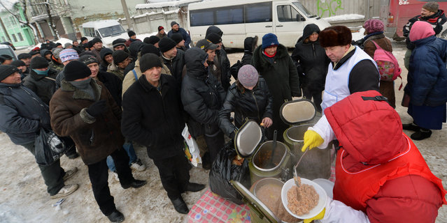 Homeless people queue to get free hot food organized by social services during a  frosty winter's day in  Kiev on December 18, 2012. Nineteen people died of exposure in Ukraine in the last 24 hours amid temperatures of minus 20 degrees Celsius (minus 4 degrees Fahrenheit), bringing the toll this month to 37, the health ministry said Tuesday. (Photo by Sergei Supinsky/AFP Photo)