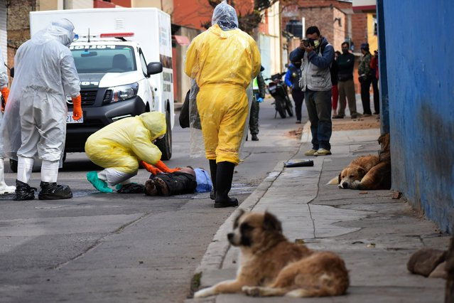 State department health workers recover the body of a street vendor who was found at dawn by his neighbors in the Cerro San Miguel neighborhood of Cochabamba, Bolivia, Saturday, July 25, 2020. As part of a government mandated protocol to curb the spread of the new coronavirus, health officials are being called on to disinfect and take COVID-19 rapid tests from the increasing number of bodies they are called on to collect, regardless on whether they are known to have been infected with the virus. (Photo by Dico Solis/AP Photo)