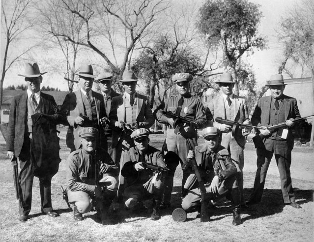 Police officers who aided in the capture of the notorious Dillinger gang in Tucson, Ariz., pose with five sub machine guns, bullet proof vests, revolvers and ammunition taken from members of the bank robbery gang and escaped convicts, January 20, 1934. From left, standing: Det. Dallas Ford; chief of police Gus Wellard; Harry Foley; Frank Eyman; Captain Jay Smith; Chet Sherman; James Herron. From left, kneeling: Milo Walker, K. Mullaney and Earl Nolan. (Photo by AP Photo)