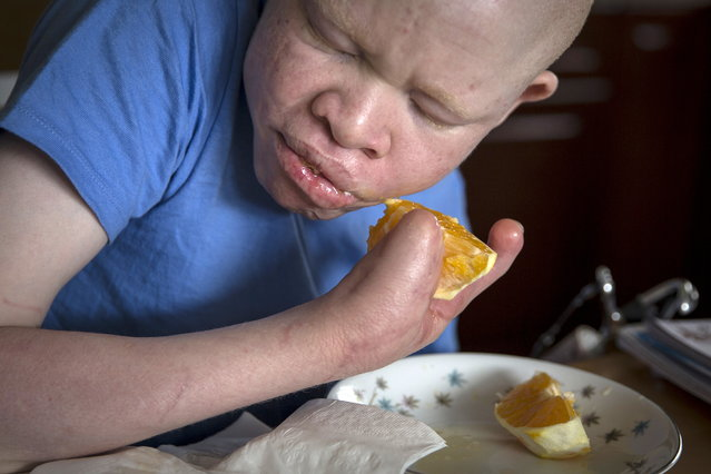 13-year-old Emmanuel Festo from Tanzania eats an orange as he does homework in Staten Island. (Photo by Carlo Allegri/Reuters)