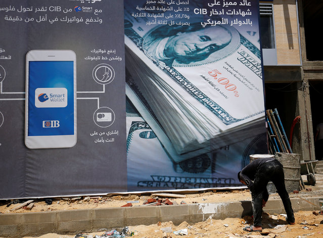 """A construction worker is seen in front of the construction of a new """"CIB"""" Commercial International Bank building covered with an image of the U.S. dollar in Cairo, Egypt July 26, 2016. (Photo by Amr Abdallah Dalsh/Reuters)"""