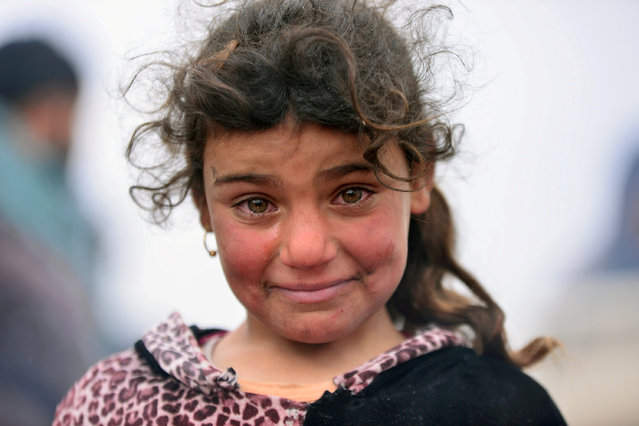 A displaced Iraqi girl, who fled her home, cries during a battle between Iraqi forces and Islamic State militants, near Badush, Iraq, March 16, 2017. (Photo by Reuters/Stringer)