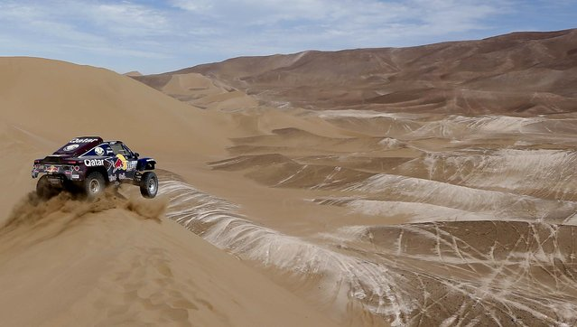 Carlos Sainz of Spain and co-driver Timo Gottschalk  of Germany compete during the 6th stage of the 2013 Dakar Rally from Arica to Calama, Chile, Thursday, January 10, 2013. Sainz and Gottschalk abandoned the race due to an engine problem. (Photo by Victor R. Caivano/AP Photo)