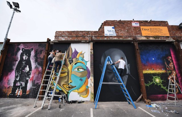 "Street artists create artworks as they take part in the ""Sand Sea & Spray"" Urban Art Festival in Blackpool, north west England on July 11, 2015. (Photo by Oli Scarff/AFP Photo)"