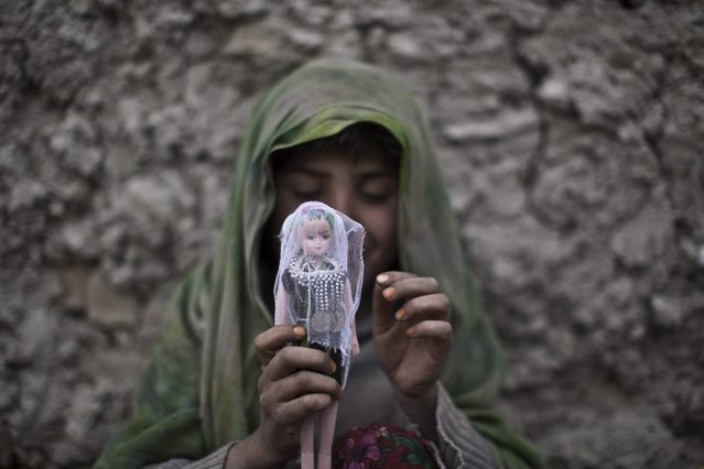An Afghan girl sits on the ground dressing her doll while playing in an alley in Kabul, Afghanistan, Thursday, April 3, 2014. (Photo by Muhammed Muheisen/AP Photo)
