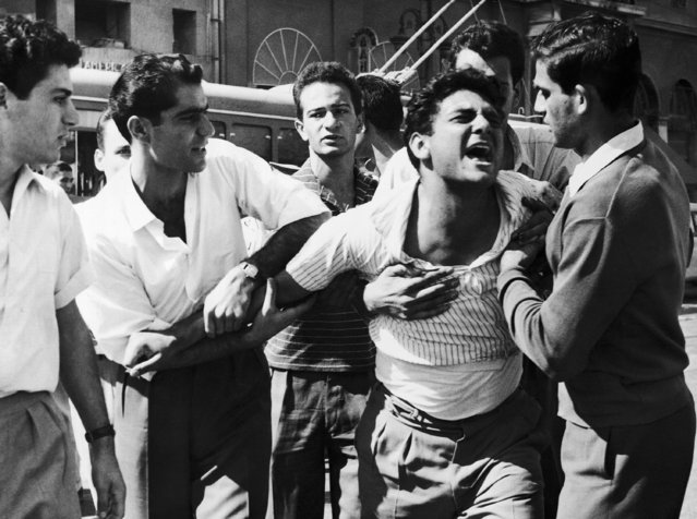 A Cypriot student screams with pain after being clubbed by policeman during demonstration at Athens University in the Greek Capital on Friday, October 7, 1958. Friends help him from the scene. Some 300 students, defying a police ban, gathered in university area in opposing application of British partnership plan in Cyprus. They tries unsuccessfully to break through a police cordon thrown around the university grounds and finally were dispersed. (Photo by AP Photo)