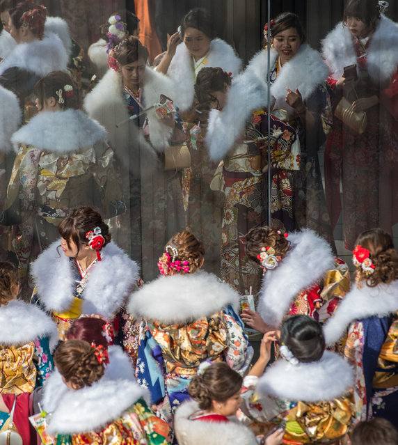 Women wearing kimonos are reflected in a window as they gather after attending a Coming of Age ceremony on January 8, 2018 in Yokohama, Japan. (Photo by Carl Court/Getty Images)