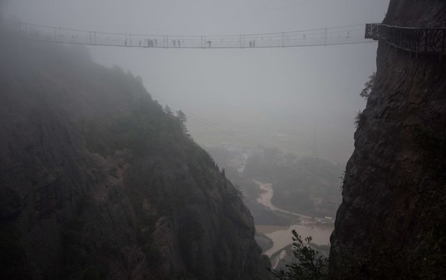 Chinese tourists walk across a glass-bottomed suspension bridge in the Shinuizhai mountains in Pingjang county, Hunan province some 150 kilometers from Changsha on October 7, 2015. (Photo by Johannes Eisele/AFP Photo)