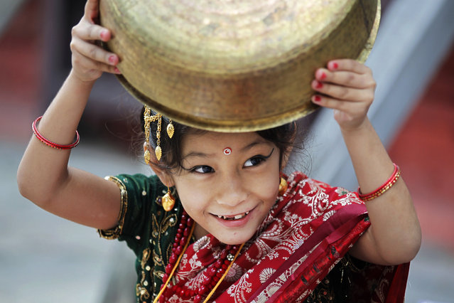 A young Nepalese girl wearing traditional attire plays with a vessel while waiting for the Kumari puja to start at Hanuman Dhoka temple, in Kathmandu, Nepal, Wednesday, September 14, 2016. Girls under the age of nine gathered for the Kumari puja, a tradition of worshiping young prepubescent girls as manifestations of the divine female energy. The ritual holds a strong religious significance in the Newar community that seeks divine blessings to save small girls from diseases and bad luck in the years to come. (Photo by Niranjan Shrestha/AP Photo)