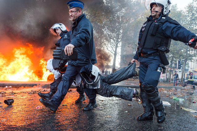 Policemen carry an arrested protestor, during a national trade union demonstration in Brussels, Thursday November 6, 2014. Tens of thousands of demonstrators are converging on the Belgian capital to protest government policies that will extend the pension age, contain wages and cut into public services. (Photo by Geert Vanden Wijngaert/AP Photo)