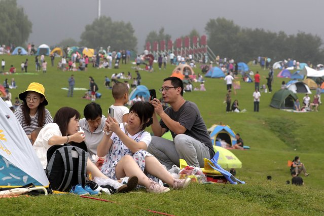 People take smartphones photos as people set camps on a scenic mountain in Yanqing, outskirt of Beijing on Sunday, August 30, 2020. China currently has more than 200 people being treated in hospital for COVID-19, with another more than 300 in isolation after testing positive for the virus without displaying symptoms. (Photo by Andy Wong/AP Photo)
