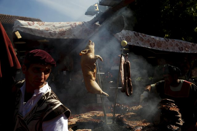 A pig hangs from a spit as it is roasted during the annual Cervantes market (Mercado Cervantino) in the hometown of famous Spanish writer Miguel de Cervantes, Alcala de Henares, Spain, October 9, 2015. The Mercado Cervantino, which represents a market and fair from the 16th and 17th centuries, takes place in the city's historic centre and commemorates Miguel de Cervantes' baptism, which took place on October 9, 1547. (Photo by Susana Vera/Reuters)