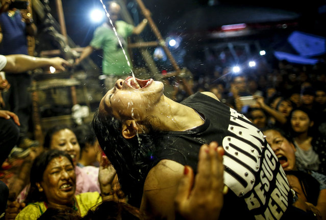 Nepalese women and young girls struggle to drink homemade alcohol poured through a pipe sticking out of the mouth of Swet Bhairab, a god of Power, during the Indra Jatra festival at Basantapur Durbar Square in Kathmandu, Nepal, 17 September 2016. Hundreds of women and young girls gathered to drink alcohol as a blessing from idol of Swet Bhairab which they believes will keep them free from all diseases. The Indra Jatra festival is celebrated to honor Indra, the king of gods and god of rains. The festival also marks the end of the monsoon. (Photo by Narendra Shrestha/EPA)