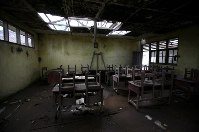 In this October 17, 2014, photo, chairs rest on tables in an empty classroom at an elementary school in the abandoned village of Simacem, North Sumatra, Indonesia. The village was abandoned after its people were evacuated following the eruption of Mount Sinabung. (Photo by Binsar Bakkara/AP Photo)