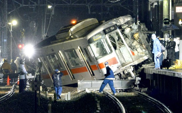 A derailed train is seen on a station platform after a collision at a railway crossing in Takasago, Hyogo prefecture, Tuesday, Feb. 12, 2013. A commuter train collided with a truck at a railway crossing in southern Japan on Tuesday, injuring more than a dozen people. (Photo by Kyodo News/AP Photo)