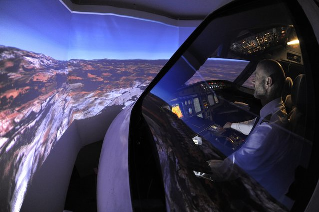 Igor Perne, 53, an electronic engineer and a member of the International Virtual Aviation Organisation (IVAO), and fellow virtual pilot Franc Lavric fly on a virtual flight in a flight simulator in Nova Vas November 13, 2014. (Photo by Srdjan Zivulovic/Reuters)