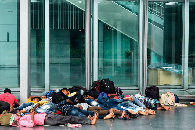 Migrant labourers rest outside the departure lounge of the Netaji Subhash Chandra Bose International Airport as their flights got cancelled during a day long state-imposed lockdown as a preventive measure against the Covid-19 coronavirus, in Kolkata on September 7, 2020. India overtook Brazil on September 7 as the country with the second highest number of confirmed coronavirus cases, even as key metro train lines re-opened as part of efforts to boost the South Asian nation's battered economy. (Photo by Dibyangshu Sarkar/AFP Photo)