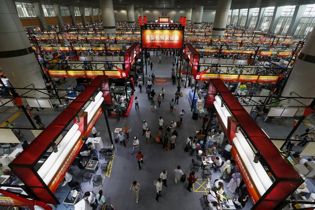 Buyers walk inside a venue for large machinery and equipment at the China Import and Export Fair, also known as Canton Fair, in the southern Chinese city of Guangzhou October 15, 2015. (Photo by Bobby Yip/Reuters)