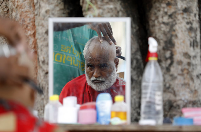 "A Hindu devotee gets a tonsure to perform ""Pind Daan"" rituals at Sangam in Prayagraj in the northern Indian state of Uttar Pradesh India, Wednesday, September 16, 2020. Pind Daan rituals are performed to bring peace and salvation to the souls of deceased ancestors. (Photo by Rajesh Kumar Singh/AP Photo)"