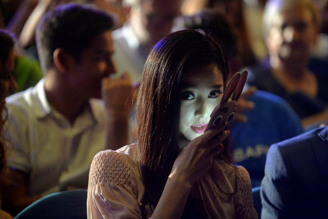 "Fan Bing Bing, Concha de Plata (Silver Shell) award winnerfor best actress for the feature film ""I Am Not Madame Bovary"" speaks on her telephone during the awards ceremony at the San Sebastian Film Festival, September 24, 2016, in San Sebastian, northern Spain. (Photo by Vincent West/Reuters)"